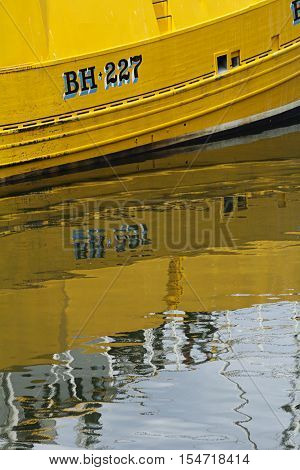 Yellow boat reflection in water. Eyemouth in Scotland UK. 07.08.2015