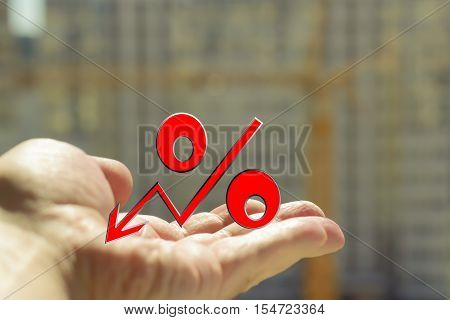 The percent symbol in the hand on a background of construction . The concept of mortgage lending .