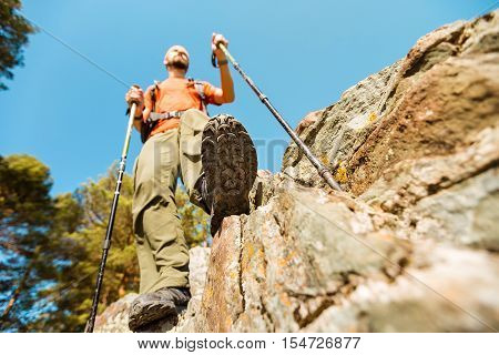 Concept, young male with beard is traveling through mountain, tourist with rucksack standing on the rock hill while enjoying nature view, summer holidays in mountains