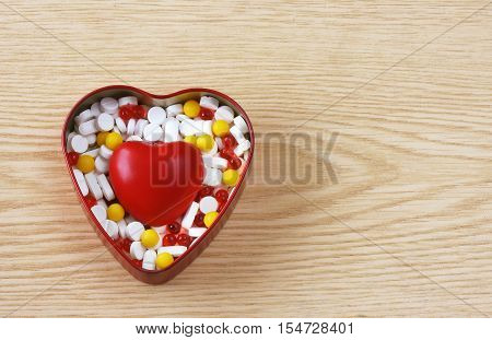 box of pills and red heart on wooden table