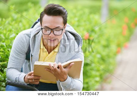 Asian student revising material before exam outdoors