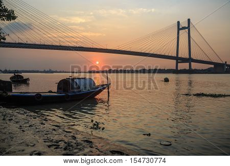 Wooden boat on river Hooghly at sunset with the Vidyasagar bridge at the backdrop. This is known to be the longest cable stayed bridge in India. (silhouette view)