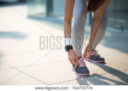 Woman tying her shoe laces before jogging