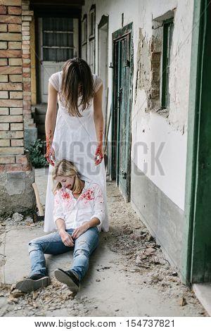 Brown hair killer woman behind dead blonde girl body