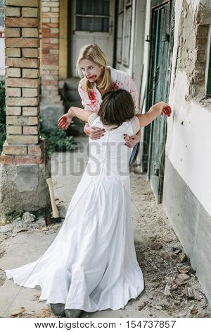 Blonde killer woman carrying dead body