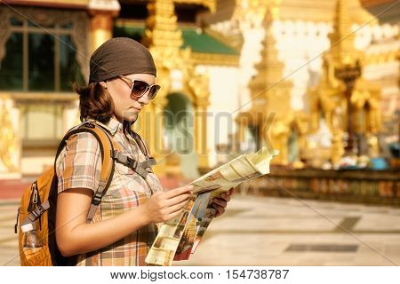 Woman traveling with backpack and looks at map temple Buddhist Shwedagon Pagoda . Myanmar