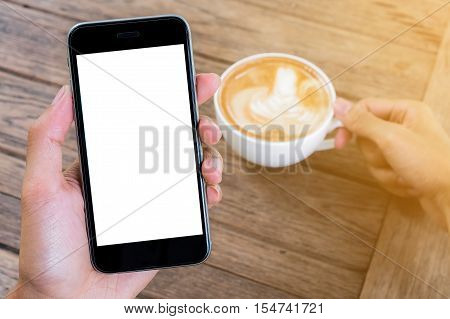 close up hand holding smart phone with laptop and stock maket chart on wood desk in coffee shop. smartphone and computer white screen and can be add your texts or others in white Space.