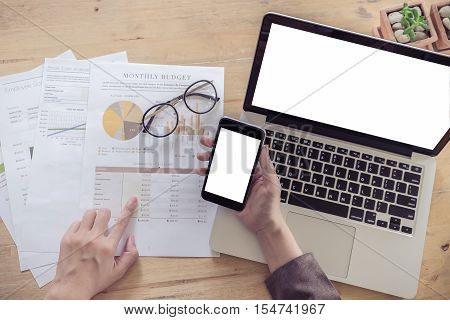 Business woman working at office hand holding smartphone with hand pointing stock maket chart and use laptop computer on his desk.