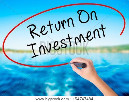 Woman Hand Writing Return On Investment  With A Marker Over Transparent Board
