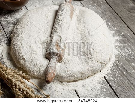 Rolling pin with flour and wheat on wooden table. Bakery background