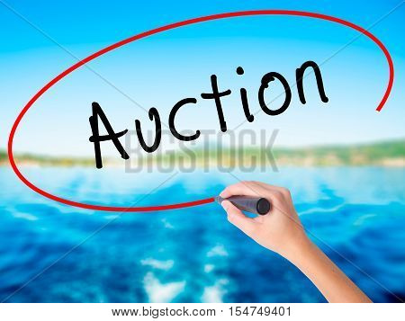 Woman Hand Writing Auction With A Marker Over Transparent Board