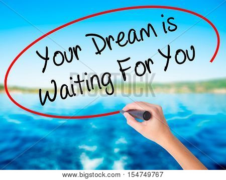 Woman Hand Writing Your Dream Is Waiting For You With A Marker Over Transparent Board