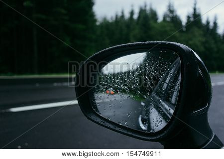 Rain drops on car side view mirror and car lights reflection. Road and forest on background