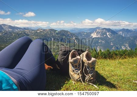 Women take off hiking shoes and relaxing on grass. Female legs boots and backpack against alpine mountains