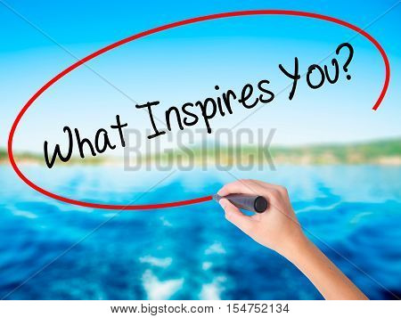 Woman Hand Writing What Inspires You? With A Marker Over Transparent Board