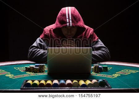 Online poker players sitting at the table. He plays on laptop. The man in the hood, do not see the face
