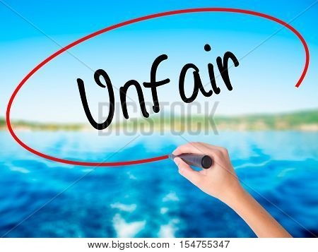 Woman Hand Writing Unfair With A Marker Over Transparent Board