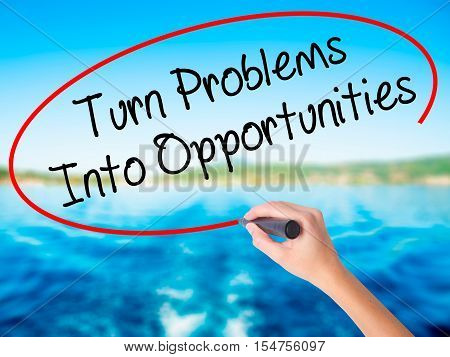 Woman Hand Writing Turn Problems Into Opportunities With A Marker Over Transparent Board.