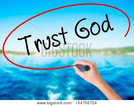 Woman Hand Writing Trust God  With A Marker Over Transparent Board