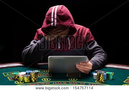 Online poker players sitting at the table. He play on tablet. The man in the hood, do not see the face. upset about losing