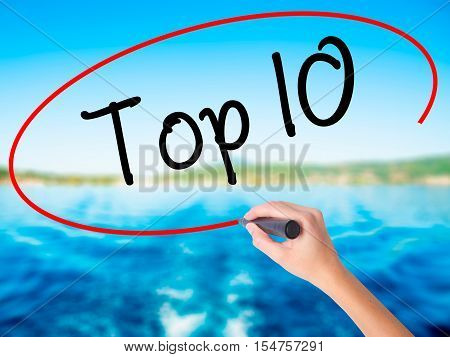 Woman Hand Writing Top 10 With A Marker Over Transparent Board