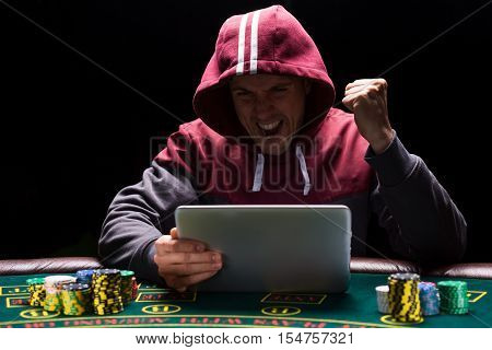 Online poker players sitting at the table. He play on tablet. The man in the hood, do not see the face. is happy victory