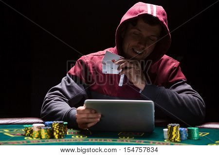 Online poker players sitting at the table. He play on tablet. The man in the hood, do not see the face. is happy victory and shows two aces