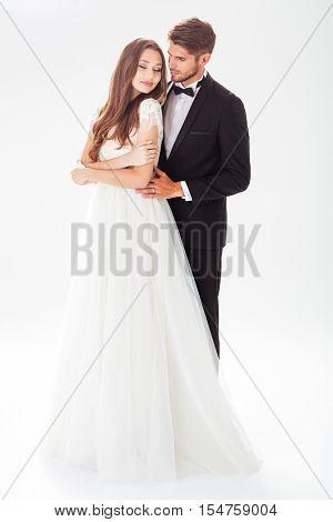 Full-length image of pretty newlyweds. white background.