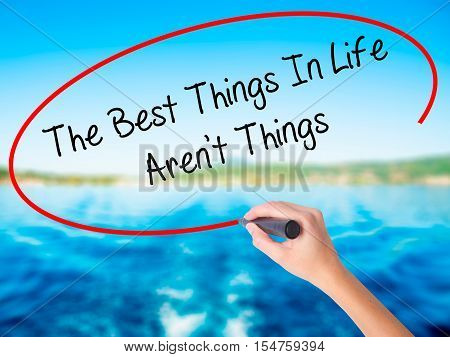 Woman Hand Writing The Best Things In Life Aren't Things With A Marker Over Transparent Board