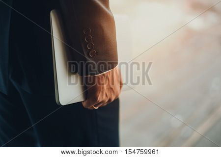 View of hand of a married business man in formal dark elegant business suit holding white laptop standing next to window of high floor blurred sunny city highway in background