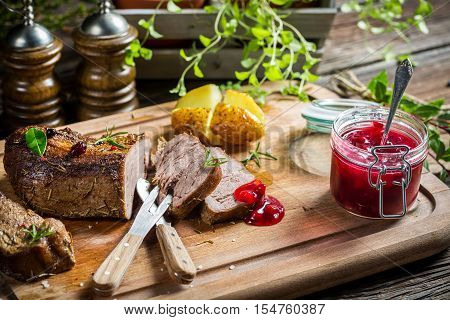 Venison with cranberry sauce and rosemary on old wooden table