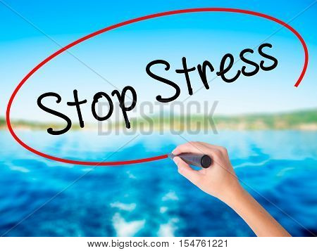 Woman Hand Writing Stop Stress With A Marker Over Transparent Board
