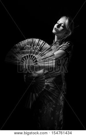 girl in japanese costume dancing with fans on black background, monochrome