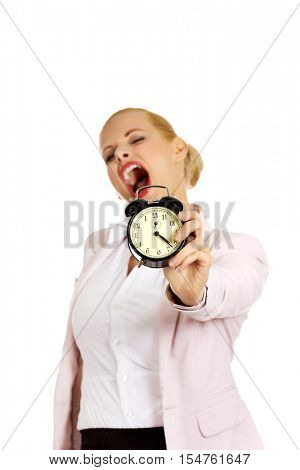 Yawning business woman holding alarm clock