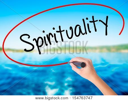 Woman Hand Writing Spirituality With A Marker Over Transparent Board