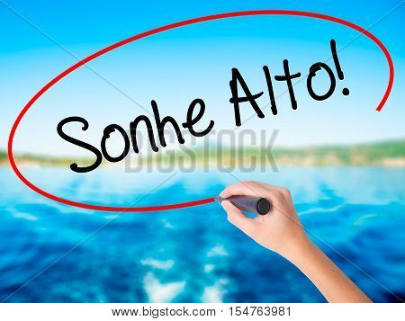 Woman Hand Writing Sonhe Alto! (dream Big In Portuguese) With A Marker Over Transparent Board