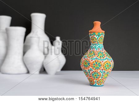 Still life of one decorated painted colorful pottery vase on background of blurred group of white vases white table and black wall