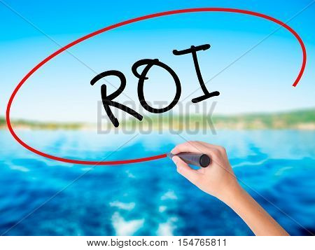 Woman Hand Writing Roi (return On Investment)  With A Marker Over Transparent Board