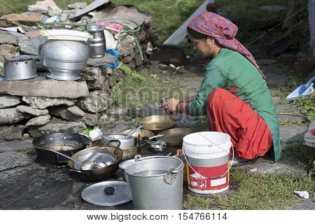 A woman cleaning utensils outdoor in Shimla, Himachal Pradesh, India.