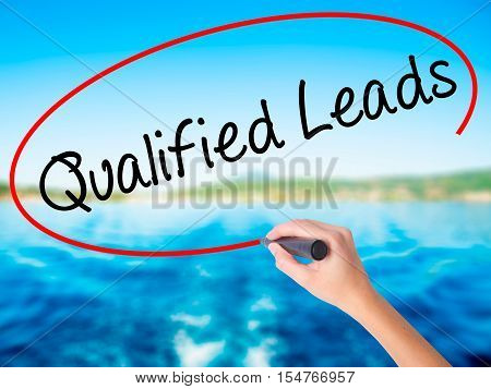 Woman Hand Writing Qualified Leads With A Marker Over Transparent Board