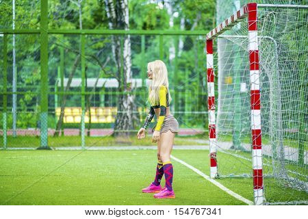 MOSCOW - JUL 16, 2015: beautiful woman (with model release) in top stands at football field at gate