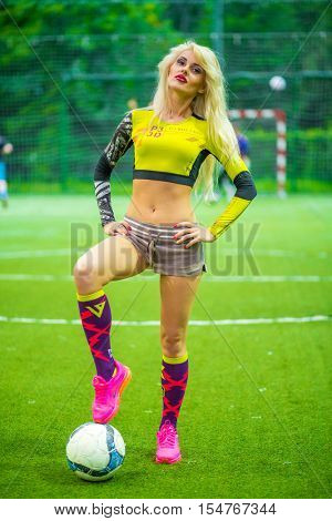 MOSCOW - JUL 16, 2015: beautiful blonde woman (with model release) in top with ball on soccer field, hands on waist