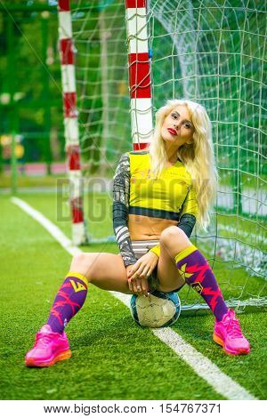 MOSCOW - JUL 16, 2015: woman (with model release) sitting on ball at gate in top on football pitch, look at camera