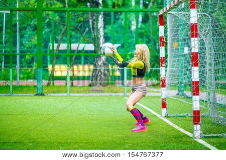MOSCOW - JUL 16, 2015: beautiful woman (with model release) in top stands at football field at gate and catch ball