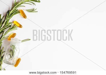 frame from rosemary, bottles, pills on white background top view.