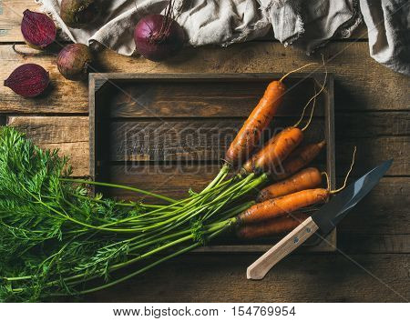 Healthy food cooking background. Vegetable ingredients. Fresh garden carrots and beetroots in wooden tray over rustic wooden background, top view, copy space, horizontal composition