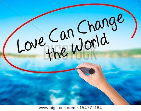 Woman Hand Writing Love Can Change The World With A Marker Over Transparent Board