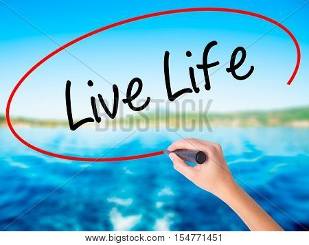 Woman Hand Writing Live Life With A Marker Over Transparent Board