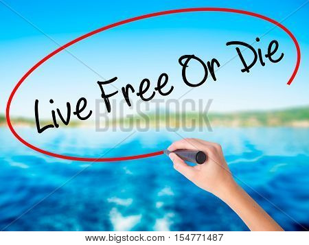 Woman Hand Writing Live Free Or Die With A Marker Over Transparent Board.