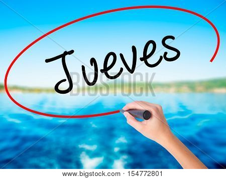 Woman Hand Writing Jueves (thursday In Spanish) With A Marker Over Transparent Board